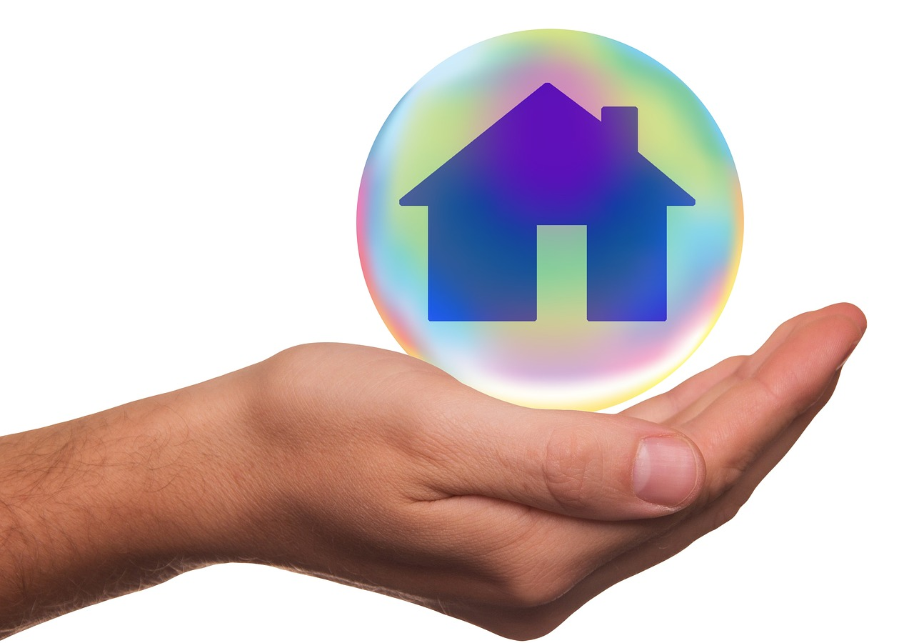 A hand protecting a home in a bubble - Home Security